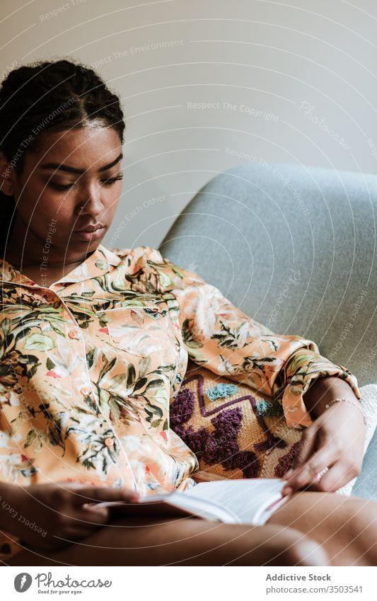 Ethnische Frau mit zu Hause ruhendem Buch heimwärts lesen Afrikanisch Amerikaner schwarz lässig Stuhl brünett Windstille Sitzen jung gemütlich ethnisch Piercing