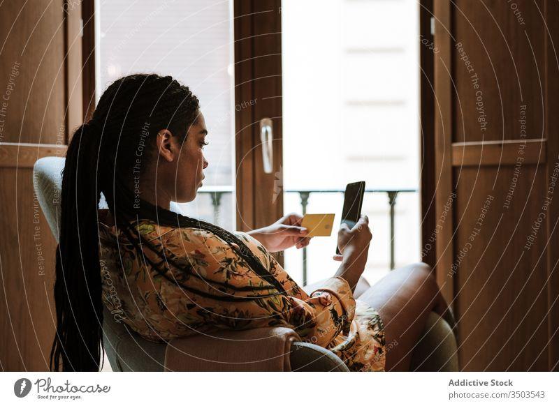 Ethnische Frau, die zu Hause online einkauft Smartphone Kreditkarte Werkstatt Zahlung Kauf heimwärts benutzend Gerät Apparatur Internet Käufer lässig praktisch