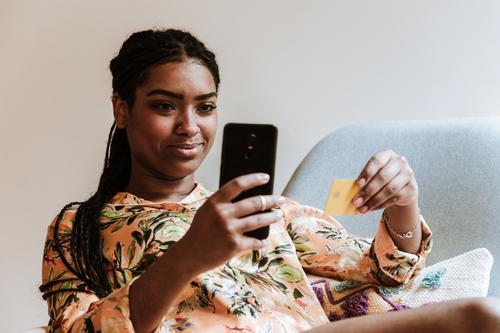 Ethnische Frau, die zu Hause online einkauft Smartphone Kreditkarte Werkstatt Zahlung Kauf heimwärts benutzend Gerät Apparatur Lächeln Internet Käufer lässig