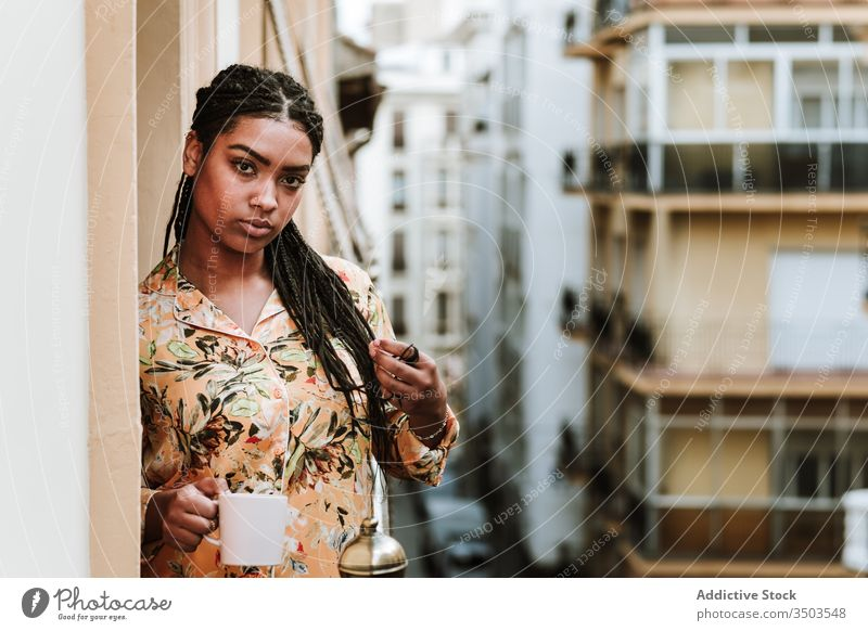 Junge Frau mit Tasse Kaffee auf dem Balkon stehend Windstille trinken lässig heimwärts ruhig nachdenklich sich[Akk] entspannen jung Afroamerikaner schwarz