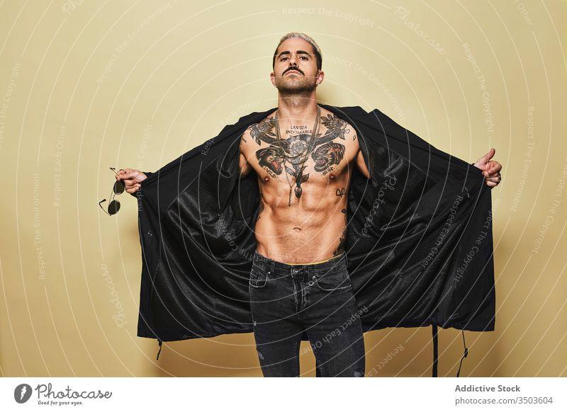 Provokativer Mann ohne Hemd mit schwarzer Sonnenbrille Macho cool trendy brutal Tattoo Stil Mode unrasiert Mantel Model Persönlichkeit muskulös Jeanshose
