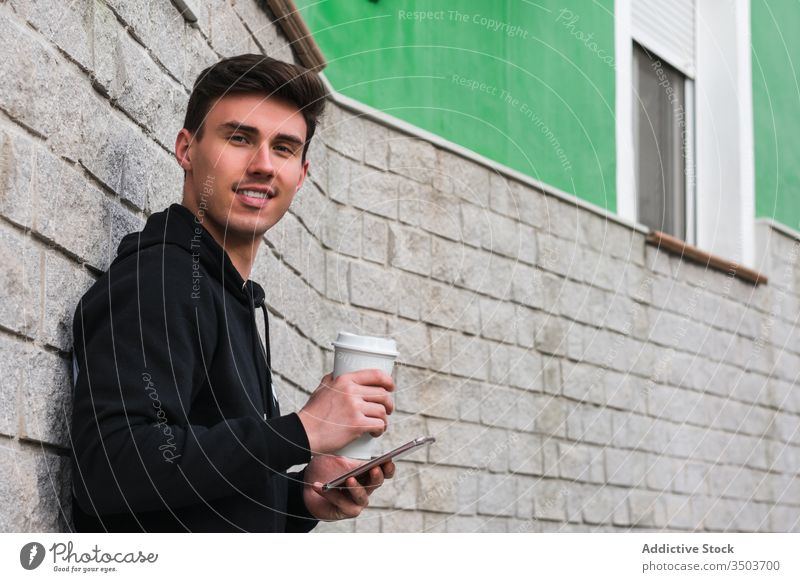 Fröhlicher Mann mit Smartphone und Getränk zum Ausruhen auf der Straße benutzend Großstadt fettarm Wand trinken zum Mitnehmen positiv männlich Gebäude jung