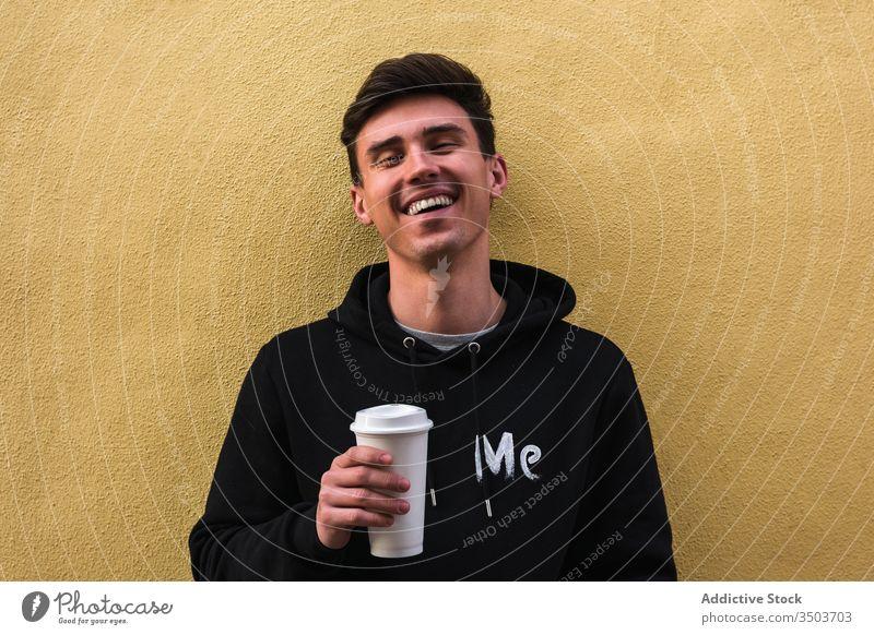 Fröhlicher Mann mit Getränk zum Ausruhen auf die Strasse Straße modern Imbissbude soziale Netzwerke Großstadt sich[Akk] entspannen Außenseite horizontal Kaffee