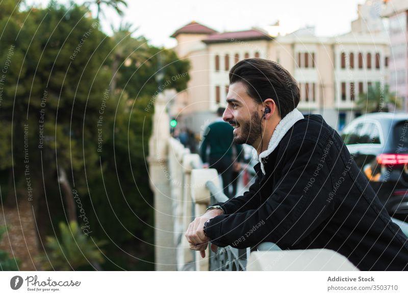 Glücklicher Mann mit Kopfhörern steht auf Stadtbrücke Großstadt zuhören Straße Brücke ruhen sich[Akk] entspannen genießen Musik Lifestyle männlich ethnisch