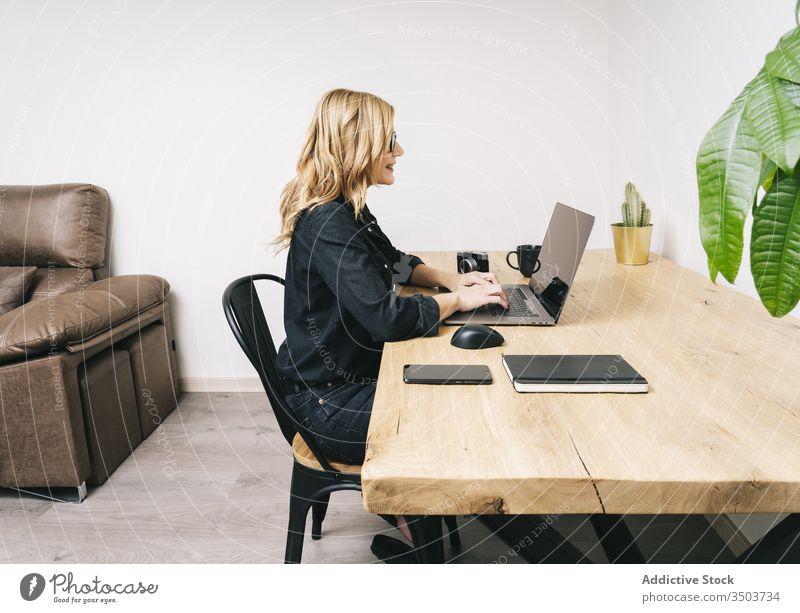 Frau arbeitet von ihrem Atelierbüro zu Hause aus heimwärts Schreibtisch Computer Business Büro Erwachsener Brille Laptop Kaukasier Browsen Tippen arbeiten