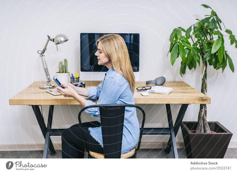 Blonde Kaukasierin arbeitet von ihrem Heimbüro aus Frau Arbeit Browsen Computer Tippen Schreibtisch heimwärts Mitteilung Geschäftsfrau Business Tablette Büro