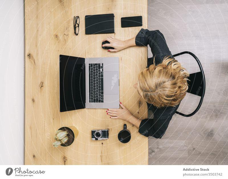 Frau, die von ihrem Atelierbüro zu Hause aus arbeitet. Computer Technik & Technologie heimwärts Business Schreibtisch Arbeitsplatz Kaffee Laptop Ansicht