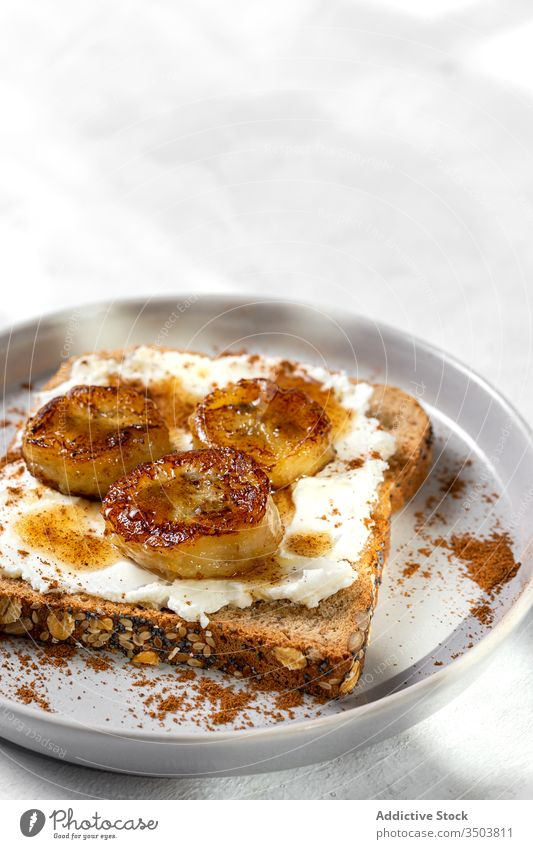 Hausgemachtes getoastetes Brot mit Frischkäse, gebratene Banane, Honig und Lebensmittel Belegtes Brot Zuprosten gebratener Wegerich Liebling Zimt Gesundheit