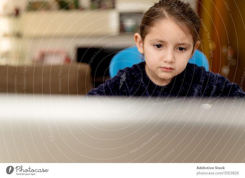 Kleines Mädchen hört dem Lehrer online zu Lektion Laptop lernen zuhören heimwärts abgelegen Aufmerksamkeit Kind Fokus Bildung Gerät Apparatur Tisch niedlich