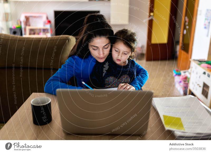 Mutter mit Tochter arbeitet an Fernprojekt freiberuflich Arbeit heimwärts Umarmung lesen Papier Laptop Tisch Frau Mädchen beschäftigt Projekt Kind Zusammensein