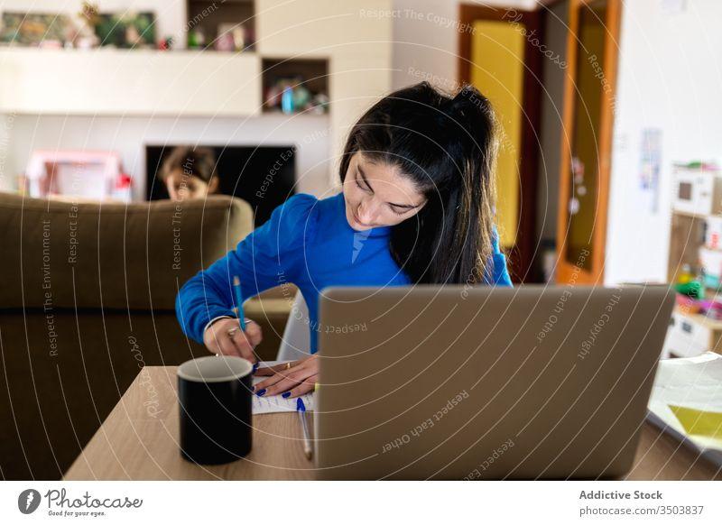 Weibliche Freiberuflerin, die zu Hause arbeitet Frau freiberuflich heimwärts schreiben Hinweis Papier Fokus Arbeit Projekt abgelegen Laptop Tisch Job gemütlich