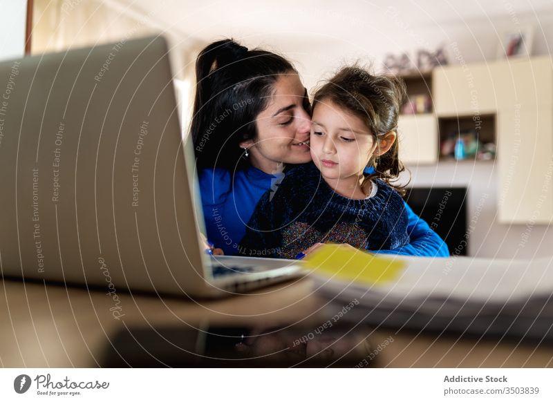 Mutter spielt mit Tochter und arbeitet an Fernprojekt spielen Umarmung Arbeit Laptop benutzend abgelegen heimwärts belästigen Liebe Frau Mädchen wenig