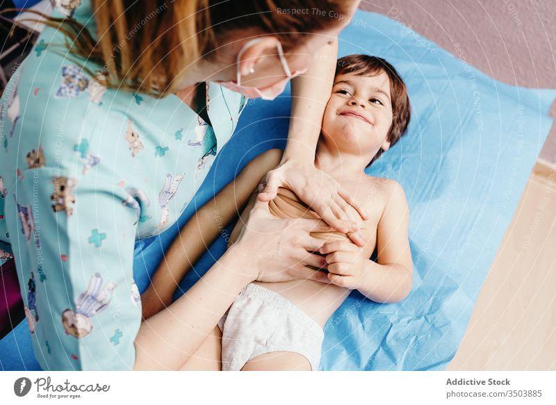 Krankenschwester untersucht kleinen Jungen in der Klinik Kind untersuchen Krankenpfleger Arzt heiter wenig Lügen Frau geduldig Krankenhaus Truhe