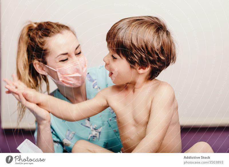 Glückliche Krankenschwester und Kind in der Klinik heiter Arzt Krankenpfleger untersuchen Junge wenig Frau geduldig Krankenhaus positiv Mundschutz Pflege