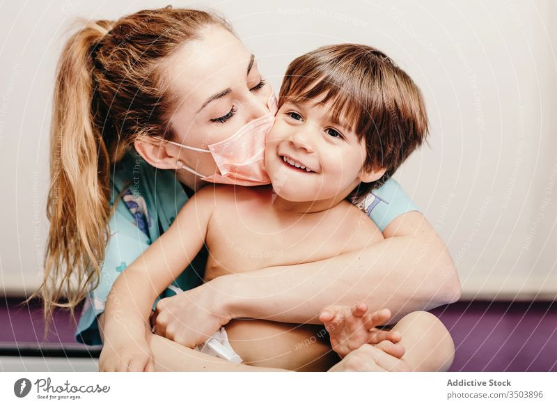 Glückliche Frau mit medizinischer Maske küsst Kind Mundschutz Kuss geduldig Klinik Art Liebe Umarmung verhindern behüten Virus Zusammensein heiter jung niedlich