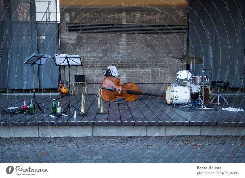 menschenleere Konzertbühne mit Notenständern, Gitarre, Trompete, Kontrabass und Schlagzeug Menschenleer notenständer Getränkeflaschen Musik Show Backsteinwand
