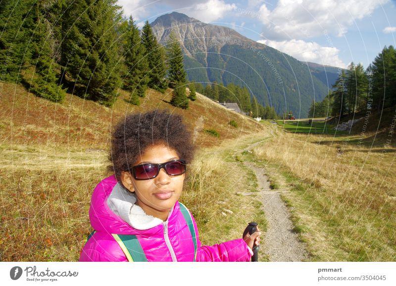 junges Mädchen lächelt glücklich auf Bergpfaden Holz Stöcke Norden Wege Natur schlendern Berge u. Gebirge Himmel blau laufen Schatten Bäume Kurven
