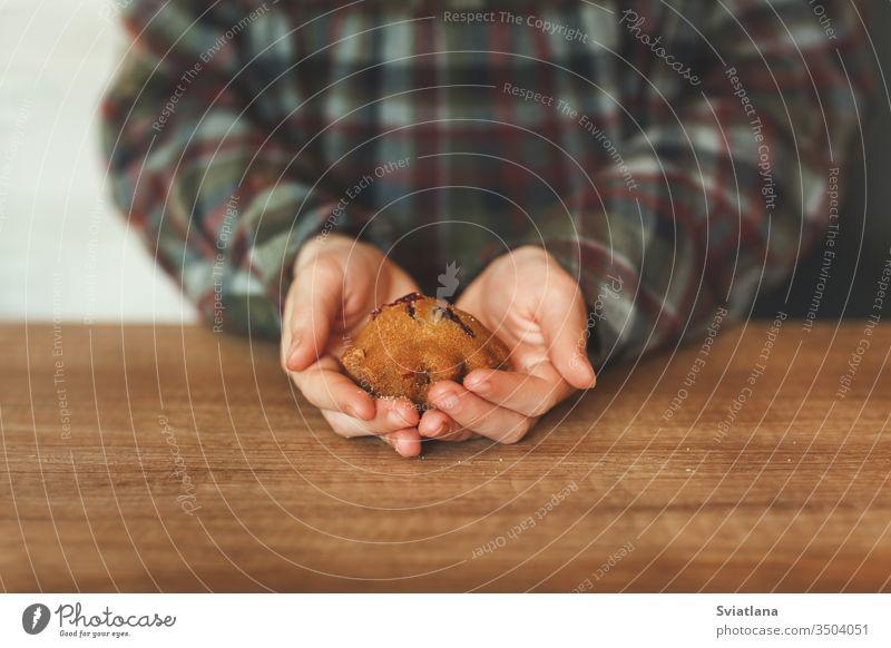 Über dem Holztisch halten Kinderhände leckere Törtchen Cupcake Lebensmittel Bäckerei Brot Dessert Gebäck Snack Zucker süß Hintergrund gebacken Beeren Frühstück