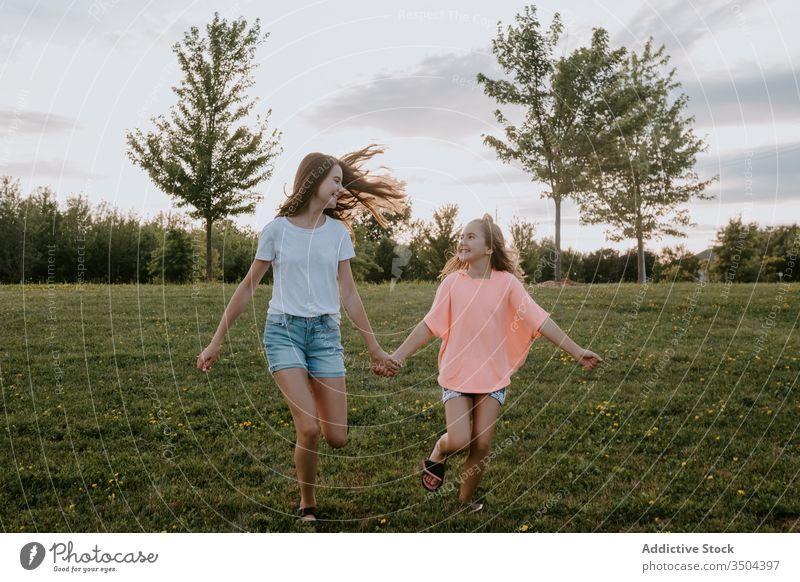 Glückliche Schwestern amüsieren sich im Sommer auf dem Land Kind Natur Zusammensein Spaß haben Mädchen Landschaft heiter laufen Teenager grün Wiese