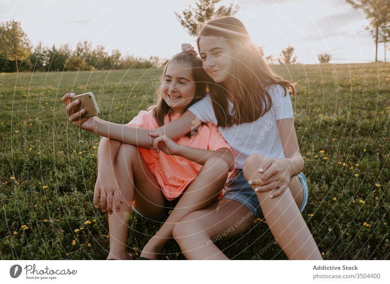 Bezaubernde Schwestern, die in einem Park sitzen und sich ein Selfie Kind Natur Zusammensein Glück Umarmung Gras Sommer Mädchen Landschaft heiter Teenager grün