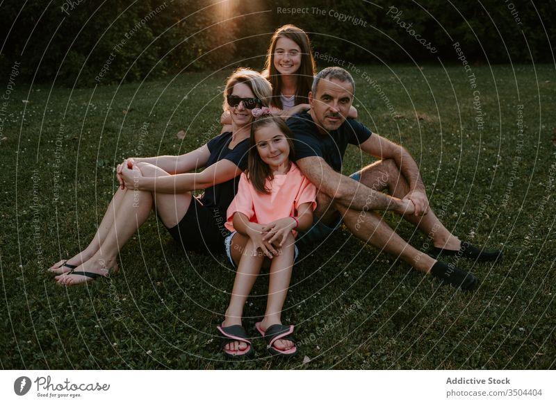 Glückliche Familie ruht sich auf der grünen Wiese aus Zusammensein Natur ruhen sich[Akk] entspannen sitzen Park Wald Landschaft Sommer Lächeln aktiv lässig Gras