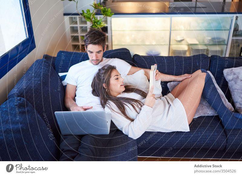 Junges Paar ruht sich zu Hause auf gemütlichem Sofa aus heimwärts Zusammensein ruhen Buch Laptop benutzend lesen jung Partnerschaft Ehemann Liege Gerät