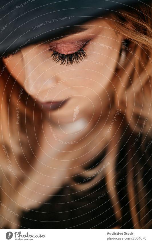 Trendige Dame, die den Hut berührt und nach unten schaut Frau Stil berühren Make-up dunkel Vorschein Maniküre Mode ernst Model Glamour Accessoire trendy