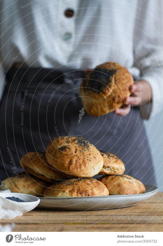 Pflanzenkoch mit frischen Brötchen Küchenchef Bäckerei Mohn Teller Samen Tisch vorbereiten Gebäck Lebensmittel lecker geschmackvoll Mahlzeit süß kulinarisch