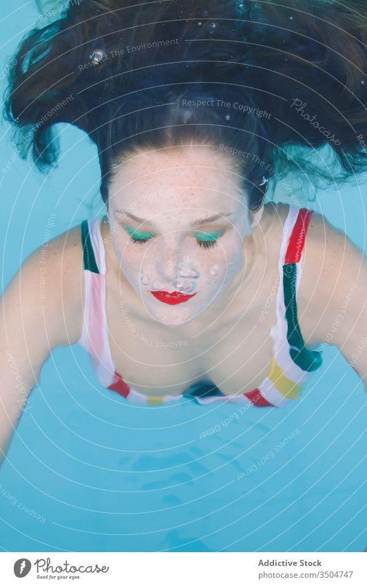 Nahaufnahme eines brünetten Mädchens mit Haaren, das mit geschlossenen Augen in den Pool getaucht ist Wasser blau Freizeit Teenager jung Treppe Frau Person
