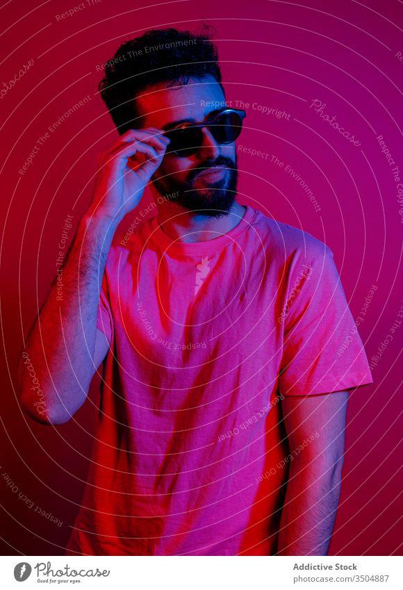 Ernster bärtiger Kerl, der eine Sonnenbrille anpasst Mann modern Stil ernst ausrichten Vollbart Rotlicht hell Outfit männlich trendy T-Shirt Bekleidung