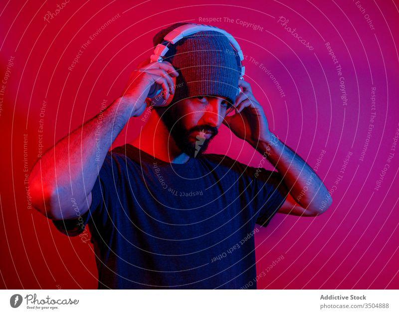Bärtiger Mann hört Musik über Kopfhörer zuhören Stil modern Vollbart Rotlicht hell Nachtleben männlich leuchten neonfarbig Gerät pulsierend Apparatur Klang