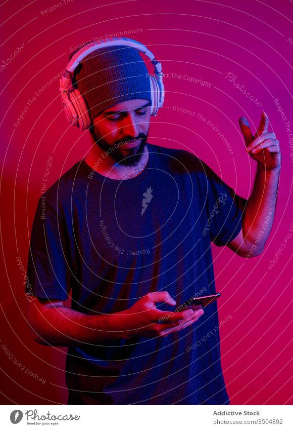 Der moderne Mensch benutzt ein Smartphone und hört Musik Mann zuhören benutzend Shaka-Zeichen Stil Handy Rotlicht männlich Gerät Apparatur gestikulieren