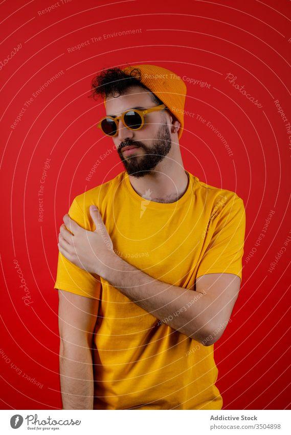 Selbstbewusster bärtiger Mann in trendigem Outfit Stil modern urban selbstbewusst Schulter berühren jung farbenfroh hell männlich Hipster ernst trendy lässig