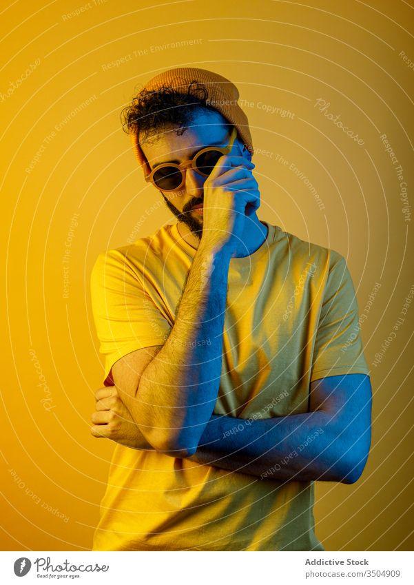 Selbstbewusster bärtiger Mann unter gelber Beleuchtung modern lässig Stil Gesicht berühren ernst Vollbart gelbes Licht hell Outfit männlich trendy Hut T-Shirt