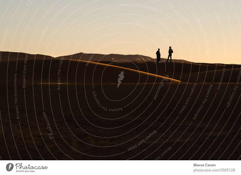 Silhouette von zwei Menschen in den Sanddünen. Sonnenuntergang in der Wüste Sahara. im Freien wüst Person Natur reisen Freiheit majestätisch Düne Farbbild