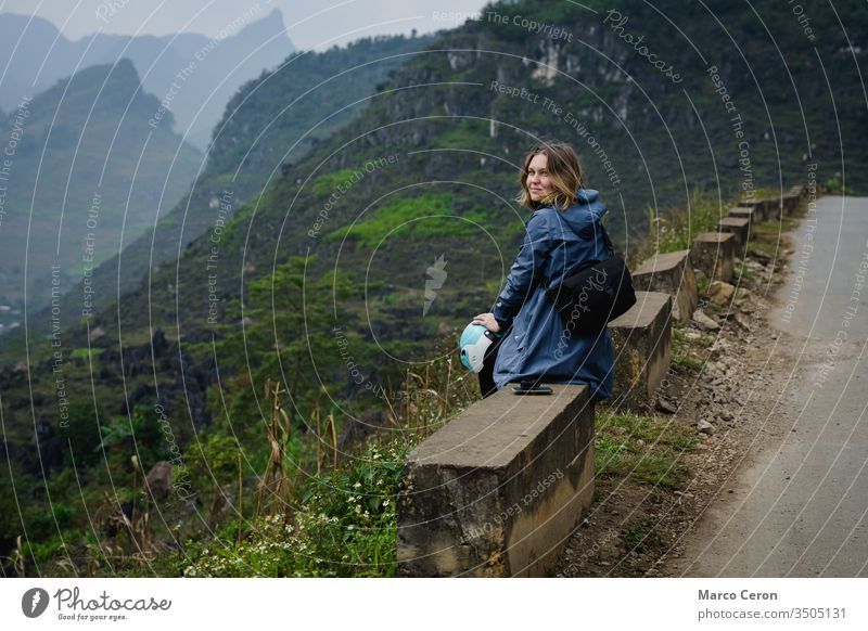 Junge Frau am Rande einer Bergstraße sitzend, Attraktive Bakpackerin, die mit dem Motorrad durch Nordvietnam fährt. Berge u. Gebirge Person Straße reisen Natur
