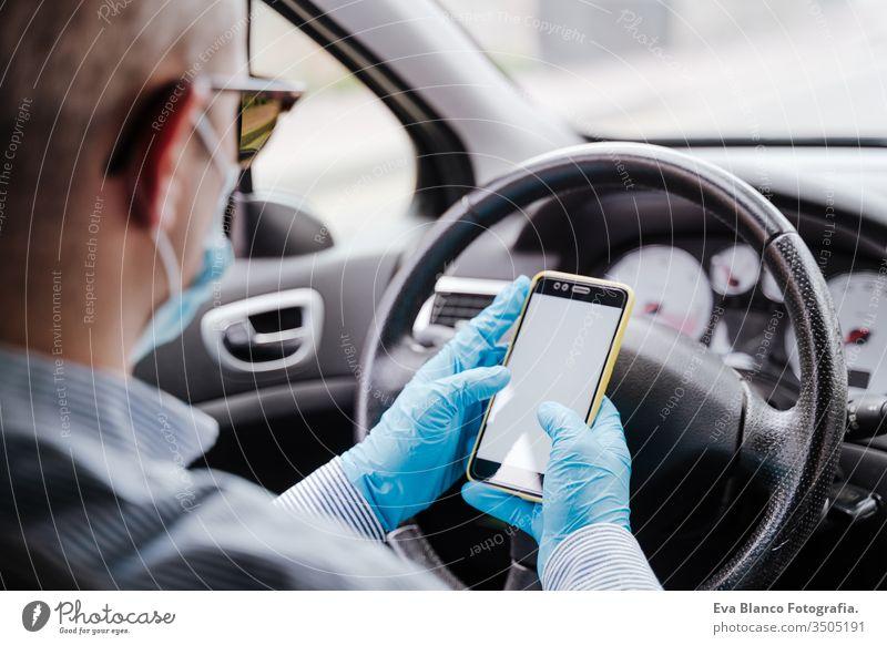 mann mit handy in einem auto mit schutzmaske und handschuhen während einer coronacirus-pandemie covid-19 Mann fahren PKW Schutzmaske Handy Schutzhandschuhe