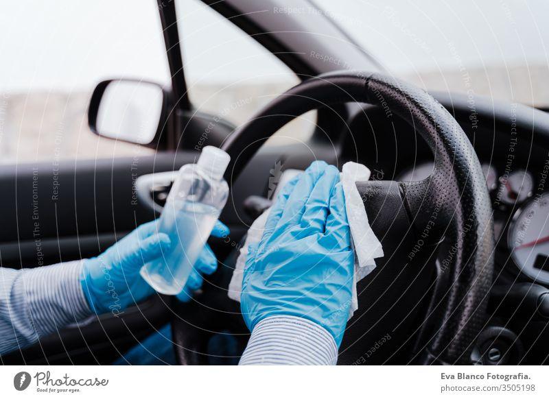 unerkannter Mann in einem Auto, der während der Pandemie des Coronavirus covid-19 Alkohol-Gel zur Lenkraddesinfektion verwendet PKW Desinfektion bekommen