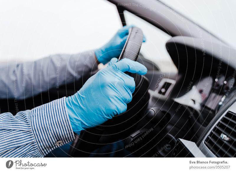nicht erkennbarer Mann am Steuer eines Autos mit Schutzmaske und Handschuhen während der Pandemie des Coronacirus covid-19 unkenntlich fahren PKW Coronavirus