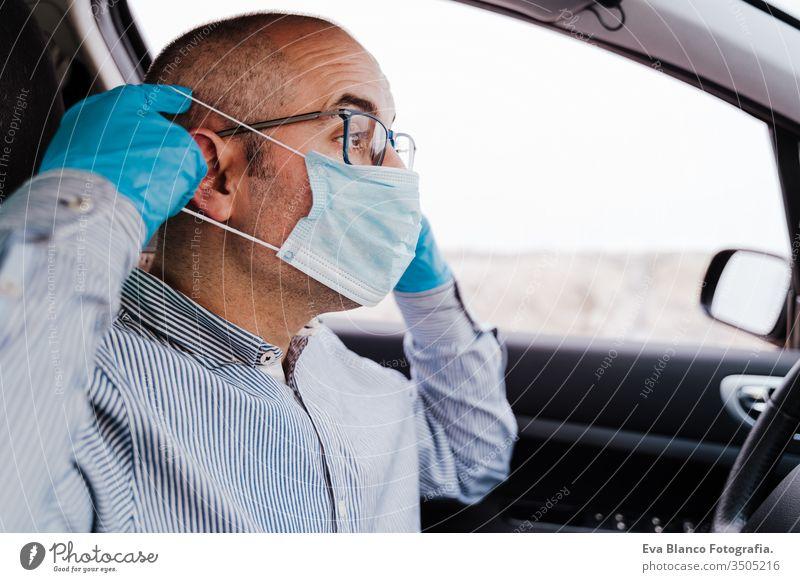 mann im auto mit schutzmaske und handschuhen während der coronacirus-pandemie covid-19 Mann fahren PKW Schutzmaske Coronavirus Pandemie Schutzhandschuhe Virus