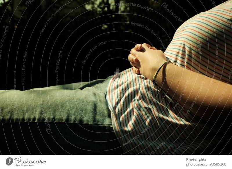 Entspannung im Garten Liege Kleidung Shirt Jeans Hose Armband Hände Arme Streifen relaxen Träumen Sommer Außenaufnahme Frau Hand T-Shirt weiß Farbfoto Mensch