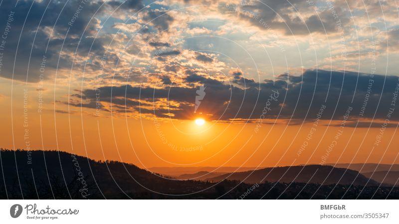 Sonnenaufgang über einigen Hügeln an einem bewölkten Morgen Hintergrund Strahl Lichtstrahl schön blau Cloud Wolken Wolkenlandschaft Farbe farbenfroh Landschaft