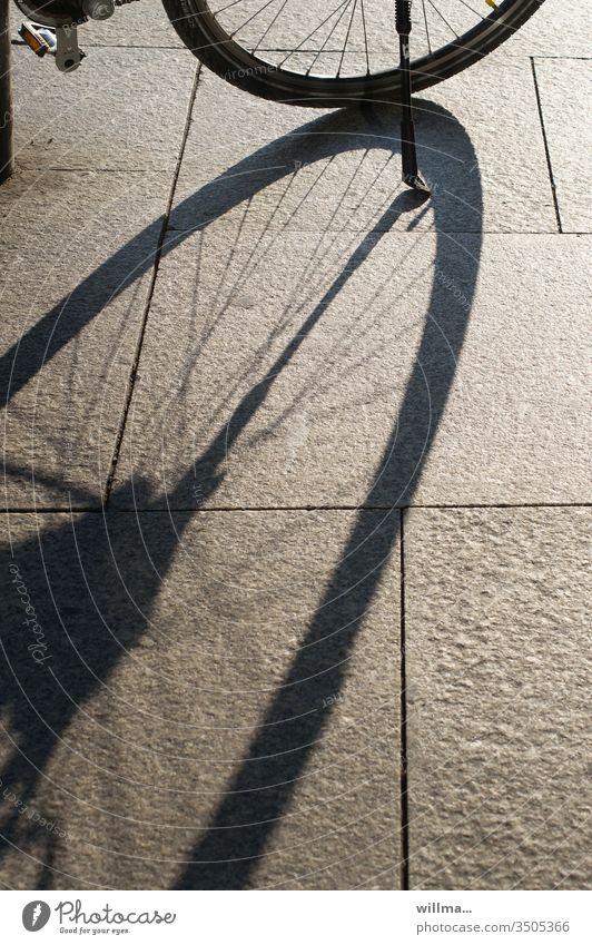 Mein Ständer wirft sehr lange Schatten Rad Fahrrad Speichen Steinplatten sonnig Fahrradständer
