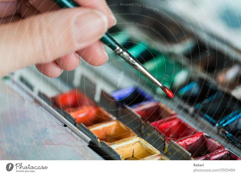 Hand hält Pinsel über Aquarellfarbe und nimmt rote Farbe auf aquarell hand mischen kunst künstler palette close up anstreichen anmalen anmischen grün bunt