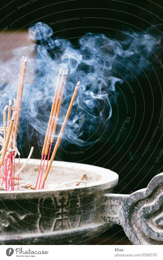 Rauchende brennende Räucherstäbchen in einer Schale vor einem Tempel Qualm räuchern ausräuchern Buddhismus Hinduismus heilig Asien Religion & Glaube