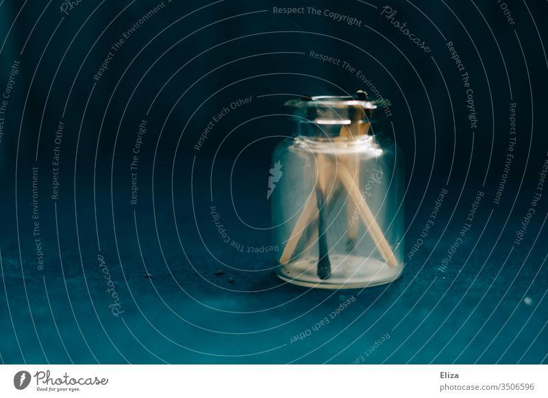 abgebrannte Streichhölzer in einem Glasfläschchen Qualm rauchen Rauch verbrannt Fläschchen Chemie Flasche schwarz dunkel verkohlt blau Rauchen