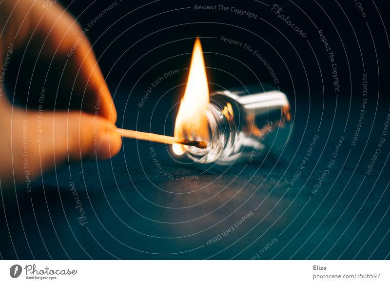 Eine Hand die mit einem brennenden Streichholz experimentiert und es in ein Apothekerfläschchen hält Flamme Phiole halten Feuer Experiment Fläschchen Flasche