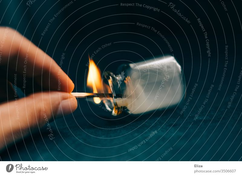 Eine Hand die mit einem brennenden Streichholz experimentiert und es in ein Apothekerfläschchen hält, in dem sich dann Rauch bildet Flamme Phiole Qualm halten