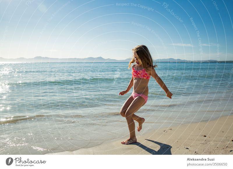 Süßes glückliches kleines Mädchen, das im Badeanzug am Strand entlang läuft und über Wellen springt. Wunderschöner sonniger Sommertag, blaues Meer, malerische Landschaft. Mallorca, Spanien