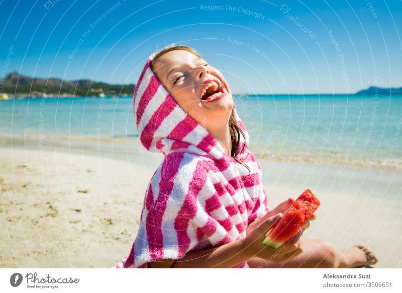 Süßes fröhliches kleines Mädchen isst Wassermelone und lacht am Sandstrand. Türkisfarbenes Meer, blauer Himmel, sonniger Sommertag. Mallorca, Spanien Aktivität